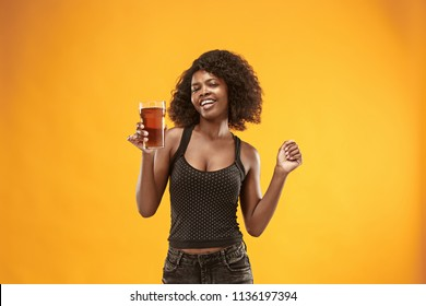 Sexy young african american woman drinking beer over orange studio background