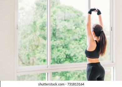 Sexy young Asian girl stretching arms exercise at fitness sport club or home gym. Yoga aerobic class, lean firm body trainer, weight loss, fat burn, or healthy lifestyle concept. With copy space