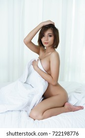 Sexy young Asian woman holding white blanket covering her naked body on bed