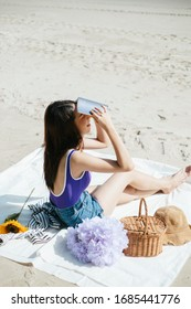 Sexy young asian woman on purple swimming suit and blue jeans sitting on a mat. Cute asian girl reading a book on the beach. Picnicking alone.