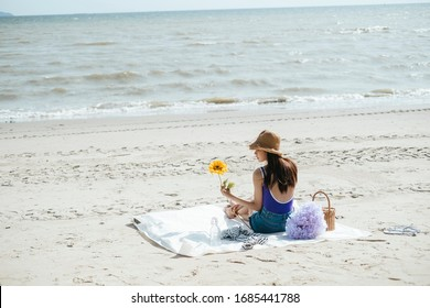 Sexy young asian woman on purple swimming suit and blue jeans holding a sunflower, sitting on a mat, picnicking alone on the beach.