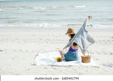 Sexy young asian woman on purple swimming suit and blue jeans sitting on a mat playing with her cloth. Young girl picnic alone on the beach.