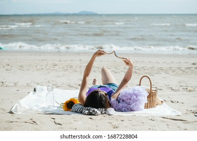 Sexy young asian woman on purple swimming suit and blue jeans laying on a mat, reading a book in the beach, sunbathing in summer season.