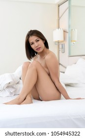 Sexy young Asian woman sitting naked on a bed in a bedroom.