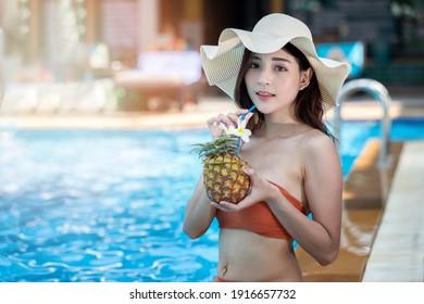Sexy junge Asiatin in Badeanzügen im Sommer. schöne Frau in orangefarbenem Bikini mit Hut im Pool mit tropischem Getränk.