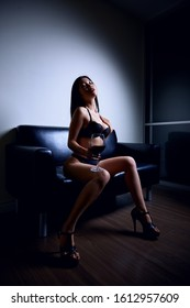 Sexy young asian woman in underwear, on a leather sofa, holding glass of wine