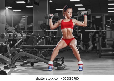 sexy young athletics girl doing dumbbells press exercises. Fitness muscled woman in red sport clothing workout on bench in gym