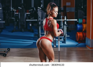 sexy young athletics girl posing with barbell on her shoulders . Fitness muscled woman in red sport clothing in gym resting after exercises