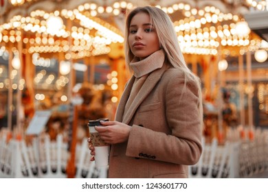 Sexy young beautiful fashion woman in a stylish autumn coat and vintage beige knitted sweater travel and drinking coffee in the amusement park. Cute girl