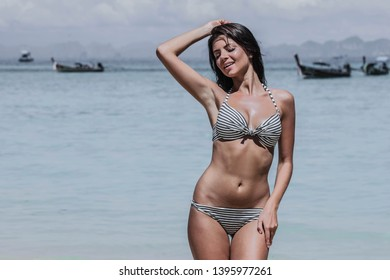 Sexy young beautiful girl in bikini on tropical beach in Thailand , long tailed boats at background