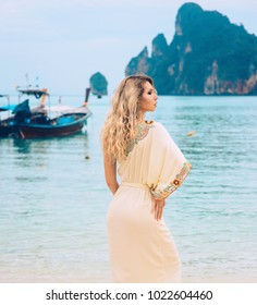 Sexy young beautiful russian girl in White dress on tropical beach in Thailand with Maya Bay. Model vacation photo shoot. Happiness summer sunrise blue sea coral white sand. Phi Phi island