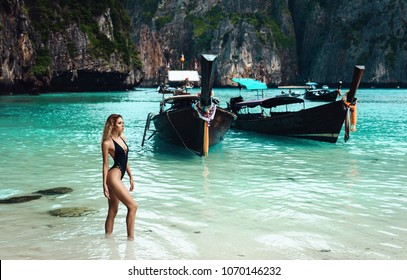 Sexy young beautiful russian girl in little bright bikini. Slim body woman on tropical beach in Thailand. Tanned skin. thai Long tailed boats at background
