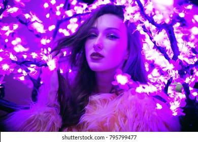 Sexy young beautiful woman posing near neon sakura tree lights dramatic ultraviolet background