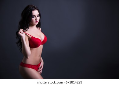sexy young beautiful woman in red lace lingerie over black background with copy space