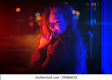 Sexy young beauty woman posing over night city dramatic red and blue neon background