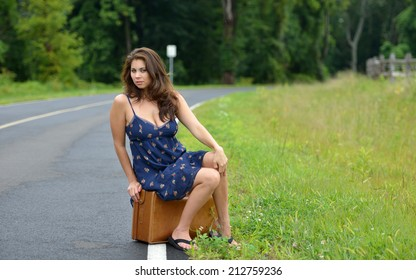 Sexy Young Biracial Asian And Caucasian Woman In Blue Dress Sitting On Vintage Suitcase