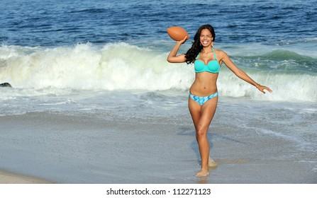 Sexy young biracial woman (Caucasian and African American) in a blue bikini on the beach smiling as she holds a football, ready to throw it