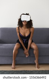Sexy young black woman using virtual reality headset for cybersex relationship or watching porn.