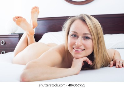 Sexy young blond naked woman sitting on the bed and smiling