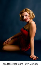 Sexy young blond woman in a red dress on a black background