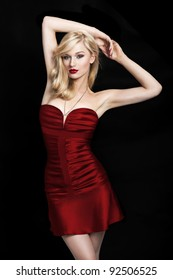 Sexy young blond woman in a red dress on a black background with her hands above the head