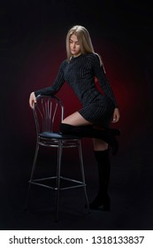 Sexy young blonde in beautiful Gray tight shiny dress with sleeves and in high suede boots posing in the studio on the chair. On a black background using red light filters