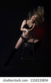 Sexy young blonde in beautiful lingerie and high suede boots posing in the studio on the chair. On a black background using red light filters without looking at the camera.