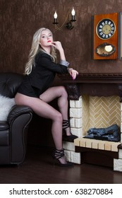 Sexy young blonde sitting in a room by the fireplace