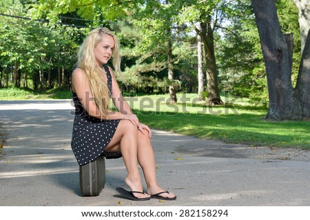 1e8330f758ac92 Sexy young blonde woman in black dress sits on a vintage suitcase outside  near road - in flip flops as well. - Image