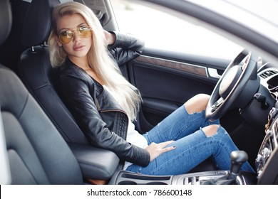 sexy young blonde woman in car. luxury car. pretty girl sitting in car. fashion and style