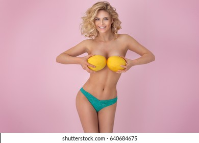 Sexy young blonde woman with perfect body posing with fresh mango, pink pastel background.