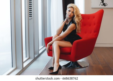 1b1755634c79 sexy young blonde woman sitting in red armchair. beautiful sexy woman with  blond hair in