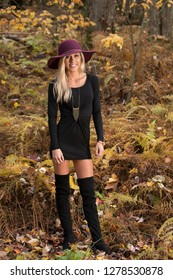 Sexy young blonde woman in stunning black dress and over the knee boots wears a colorful hat in the autumn woods - fall fashion