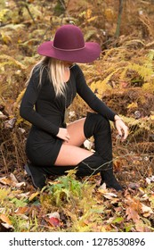 Sexy young blonde woman in stunning black dress and over the knee boots wears a colorful hat in the autumn woods - fall fashion - kneeling
