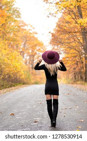 Sexy young blonde woman in stunning black dress and over the knee boots wears a colorful hat standing on deserted country woods in fall - autumn fashion