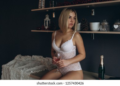 Sexy young blondie girl with stylish haircut in erotic lingerie posing, reading in the kitchen. Beauty, sexy, fashion concept