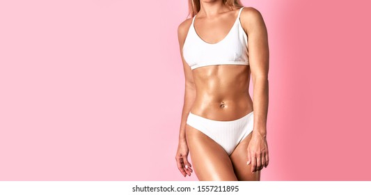 Sexy young body of unrecognizable woman in white lingerie standing against pink wall in modern photo studio, having perfect bronzed body, soft tanned skin, fitness sportive people concept