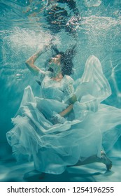 sexy young bride swimming underwater in white wedding dress, stockings and gloves