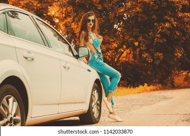 Sexy young brunette in jeans overall stans at the white car in autumn time