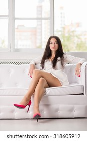 Sexy young brunette posing on the white couch