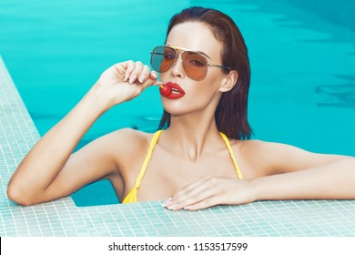 Sexy young brunette retro woman licking lollipop in swimming pool