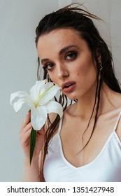Sexy young brunette woman with beautiful make up, tan sking holding lily flower while posing on white background. Skincare cosmetics, Wellness. Beauty portrait concept