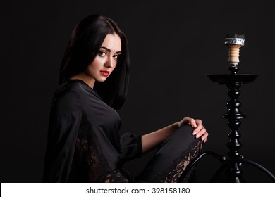 Sexy young brunette woman in black dress smoking hookah on black background. Young sexy woman in luxury dress smoking the hookah. brunette girl sitting smoking a hookah. Girl enjoying exhales.