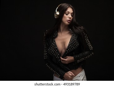 Sexy young brunette woman dancing and listening for the music using headphones