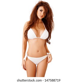 Sexy young brunette woman with large breasts posing in a white bikini  three quarter isolated studio portrait