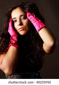 sexy young brunette woman with long curly hair wearing pink gloves