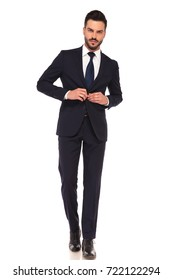 sexy young business man buttoning suit while walking on white background