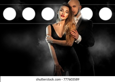 sexy young couple in black suit hugs and looks at the camera in studio on dark smoke background