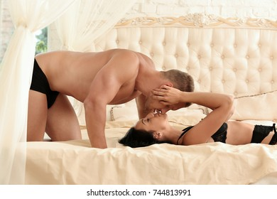 Sexy young couple kissing on bed