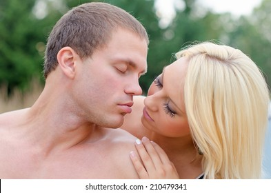 Sexy young couple kissing outdoors.